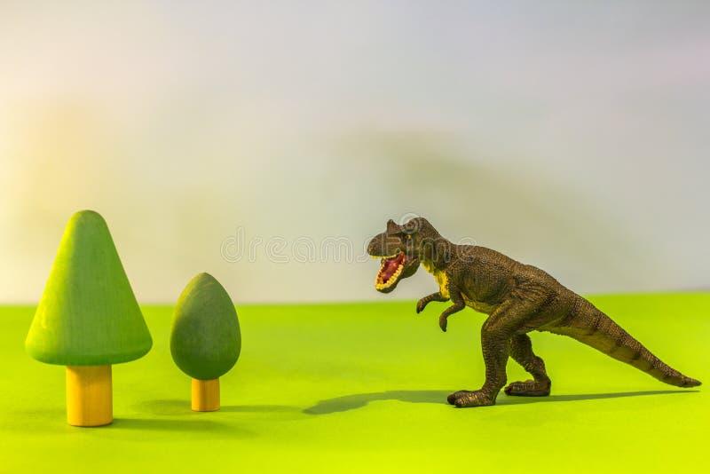 Dinosaurio del juguete en un bosque del juguete como un T-rex real en un fondo brillante del estudio con los árboles de madera Ju imagen de archivo
