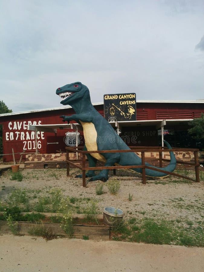 Dinosaurio delante de la entrada de las cavernas de Grand Canyon fotos de archivo