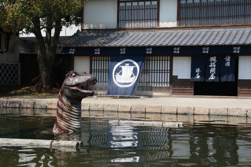Dinosaurio delante del edificio histórico en el parque del estudio de Toei Kyoto imagen de archivo libre de regalías