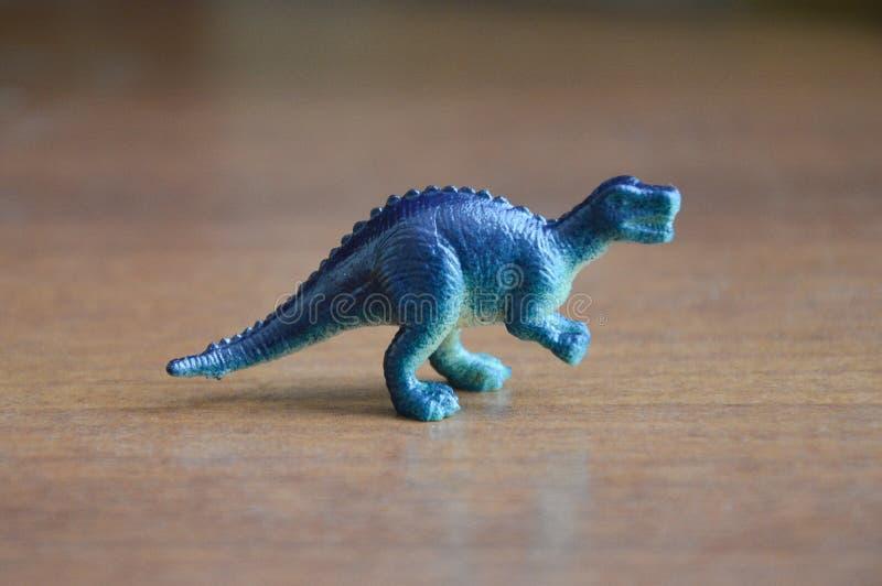 dinosaurio el juguete de los niños bajo la forma de dinosaurio en un fondo oscuro fotos de archivo