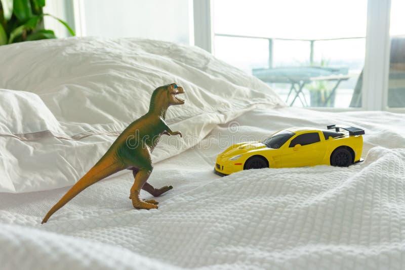 Dinosaurio y coche del juguete en la cama del padre, representando el domicilio familiar y parenting vida Linos blancos en fondo imagen de archivo libre de regalías
