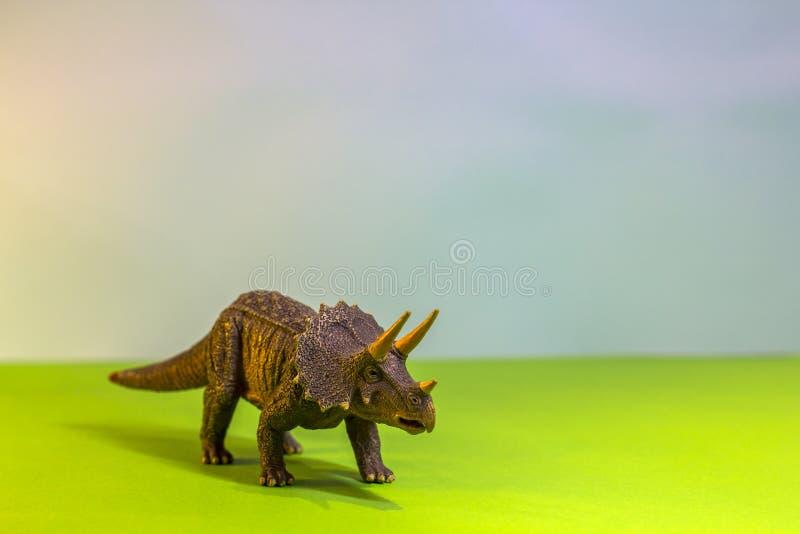 Dinosauro del giocattolo in una foresta del giocattolo come Dino reale su un fondo luminoso dello studio con gli alberi di legno  immagine stock