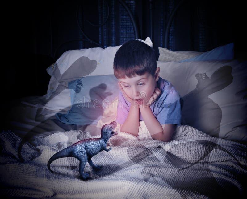 Dinossauro de T-Rex na cama assustador da criança foto de stock royalty free