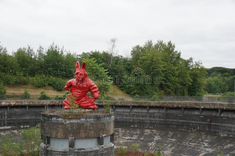 DINSLAKEN, Germany - 15/07/2019: Red Art Figure At. `Bergpark Lohberg` On A Cloudy Day royalty free stock photo