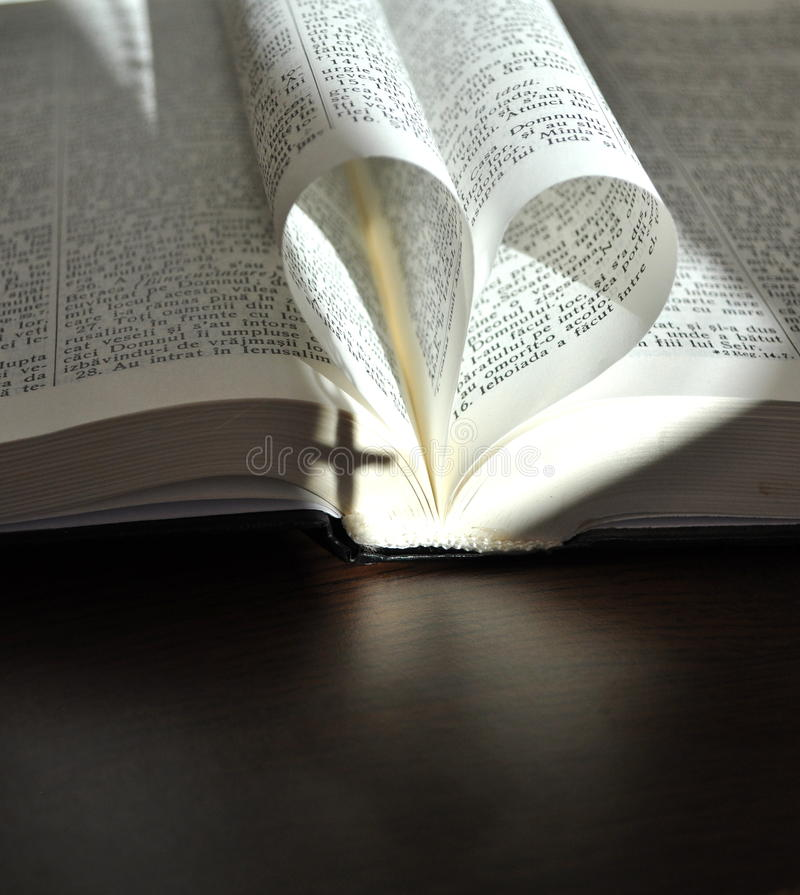 Dio è amore, pagine del primo piano di un libro aperto, con le pagine a forma di cuore immagini stock