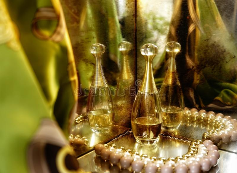 Dior bottle jewelry luxury gold pearl mirror reflection green background stock photo