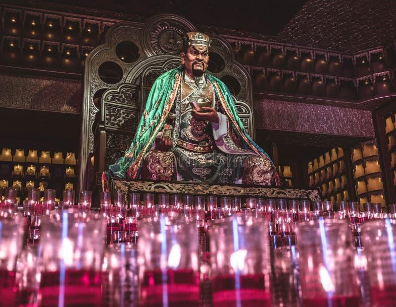 Dios asiático que se sienta con las velas rojas delante de él foto de archivo