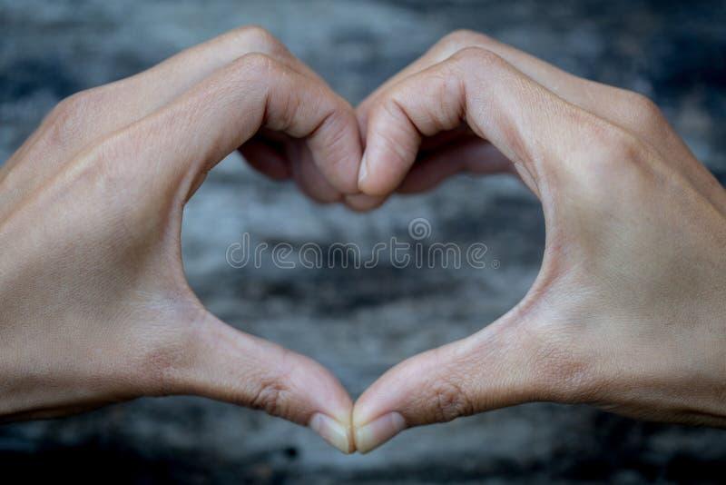Dios es concepto del amor, manos que hacen la forma y el viejo fondo de madera, símbolo del corazón del amor, manifestación del a foto de archivo libre de regalías