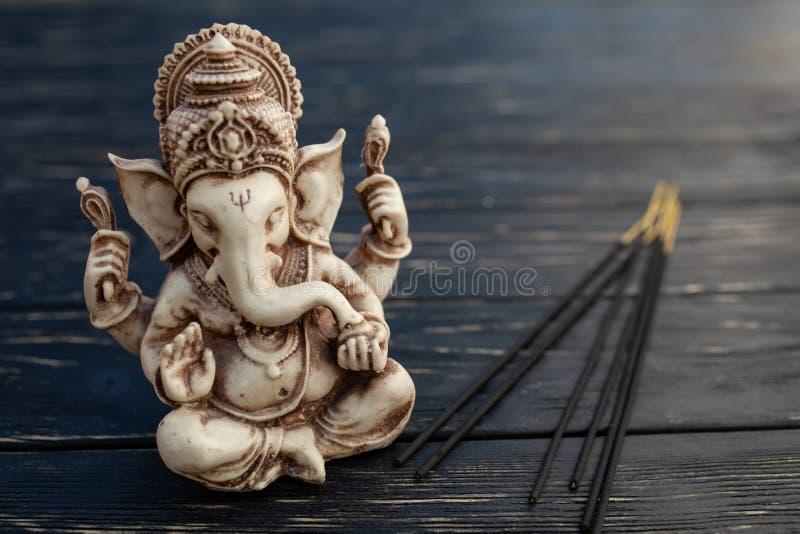 Dios hindú Ganesh en fondo negro Estatua en la tabla de madera fotos de archivo libres de regalías