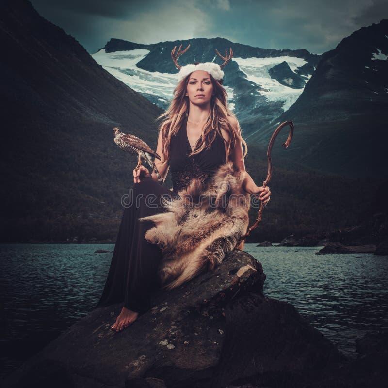Diosa nórdica en la ropa ritual con el halcón cerca del lago salvaje de la montaña en el valle de Innerdalen imagenes de archivo