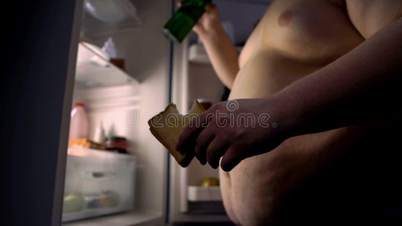 Dipendente per digiunare panino mangiatore di uomini del grasso alimentare e birra bevente vicino al frigorifero immagini stock libere da diritti