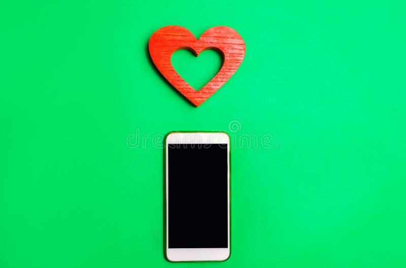 Dipendenza dalle reti sociali telefoni lo smartphone ed il cuore su un fondo verde datazione online, flirtare, messaggio e chiama fotografie stock