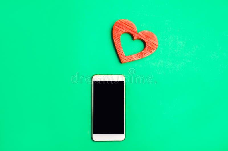 Dipendenza dalle reti sociali telefoni lo smartphone ed il cuore su un fondo verde datazione online, flirtare, messaggio e chiama fotografia stock