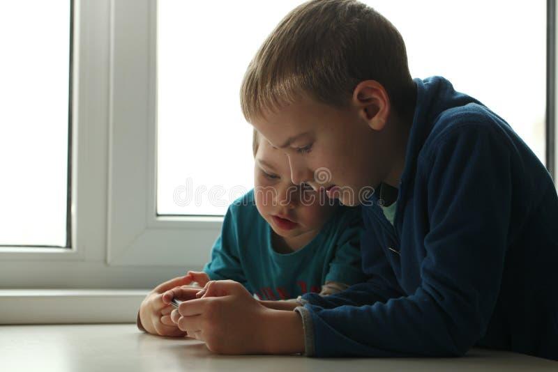 Dipendenza del gioco in bambini due bambini che giocano con uno smartphone mentre sedendosi a casa alla tavola fotografia stock