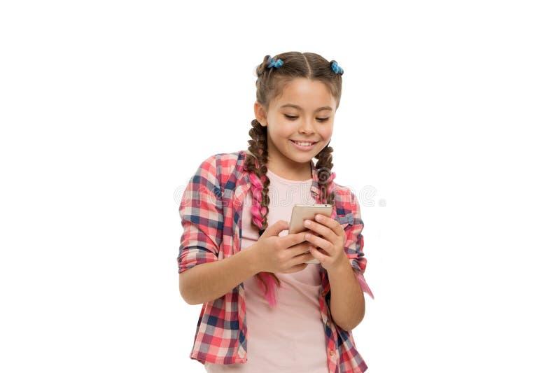 Dipendenza del telefono cellulare Bambino sveglio della ragazza piccolo che sorride per telefonare schermo Gradisce la navigazion fotografie stock