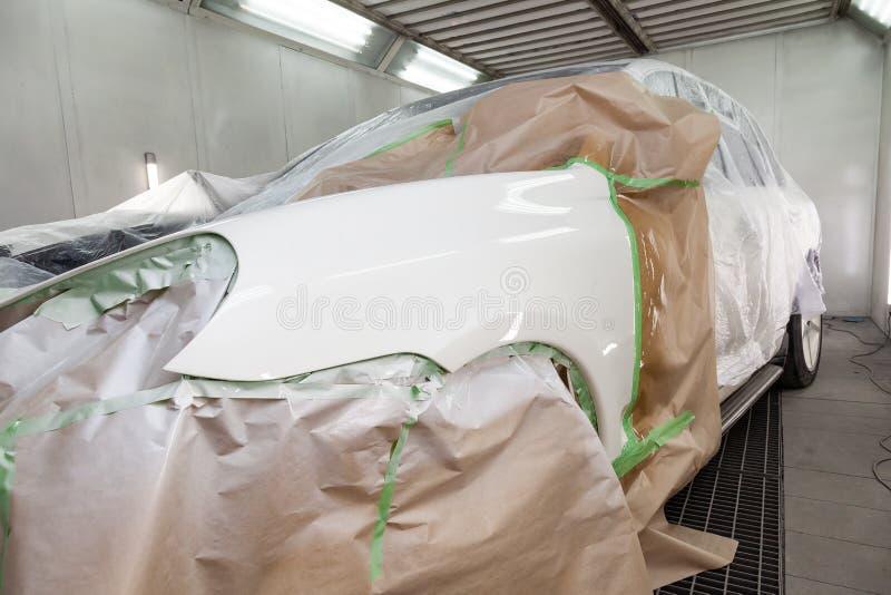 Dipingendo le parti di carrozzeria del cuscino ammortizzatore bianco dell'autista nella cabina di spruzzo nell'officina della rip fotografia stock