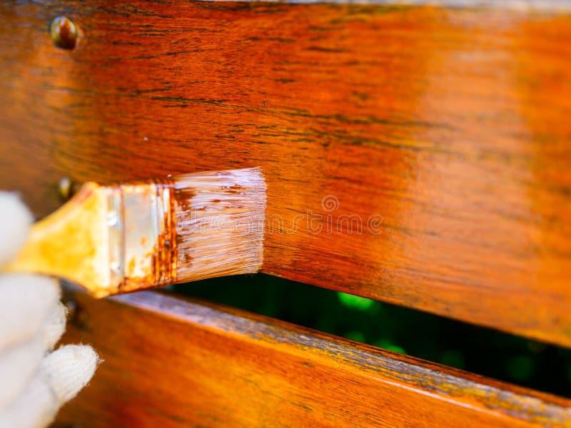 dipingendo un recinto di legno - un primo piano della spazzola, una profondità molto bassa immagine stock