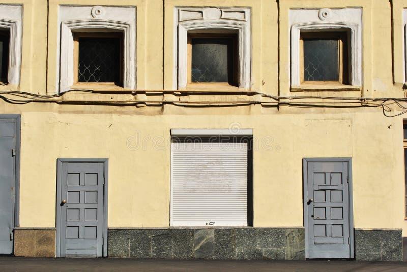 Dipinto in parete gialla di costruzione con le finestre e le porte alte imbarcate fotografia stock
