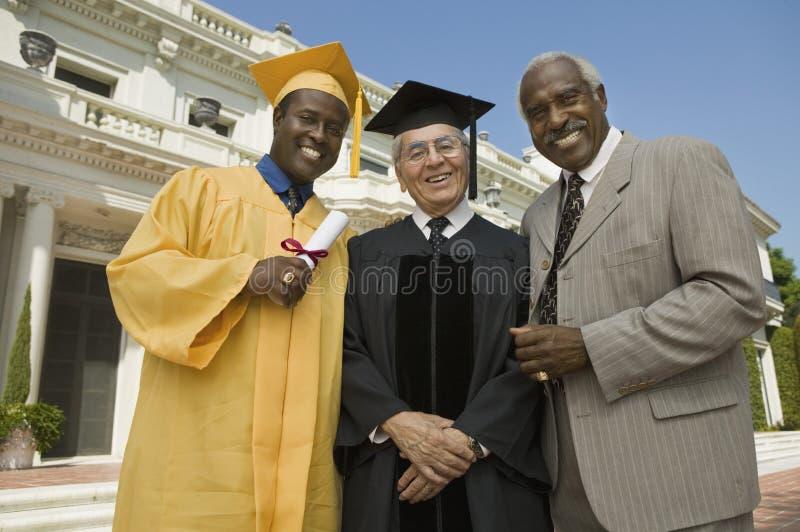 Diplômé avec le doyen et le père en dehors de l'université image stock