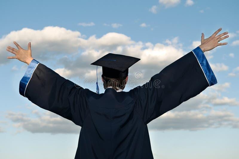 Diplômé heureux avec les bras levés photographie stock