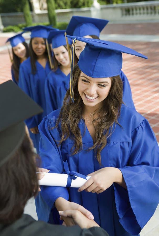Diplômés de femelle rassemblant le certificat du doyen photos libres de droits