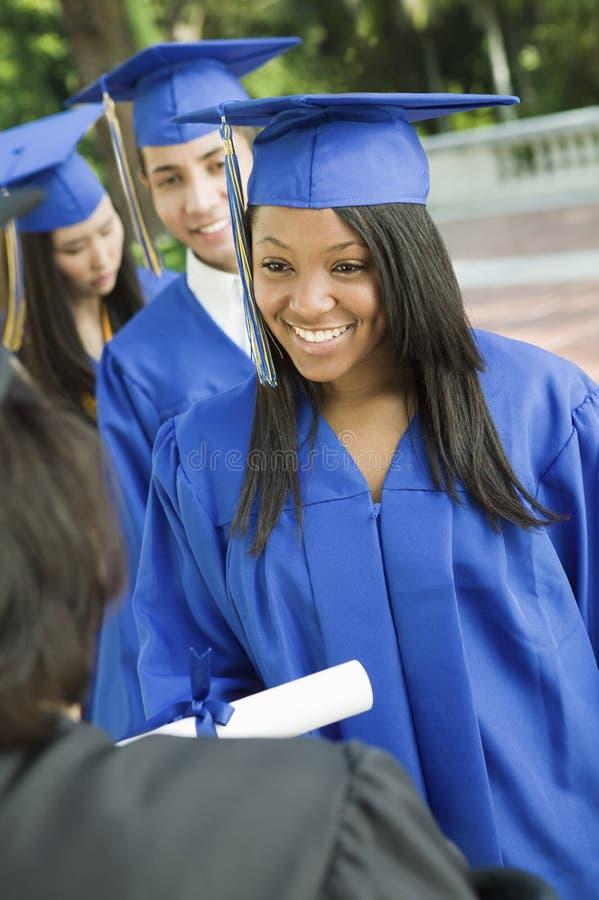 Diplômés rassemblant le certificat du doyen images libres de droits