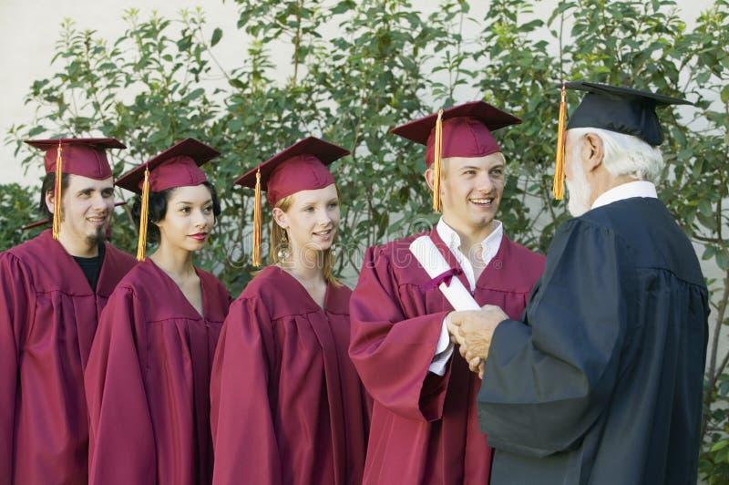 Diplômés rassemblant le certificat du doyen image libre de droits
