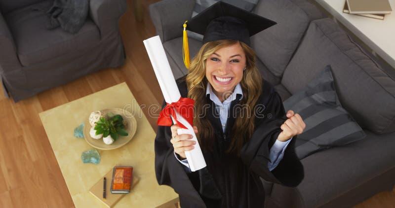 Diplôme se tenant licencié de jeune femme heureuse photo stock