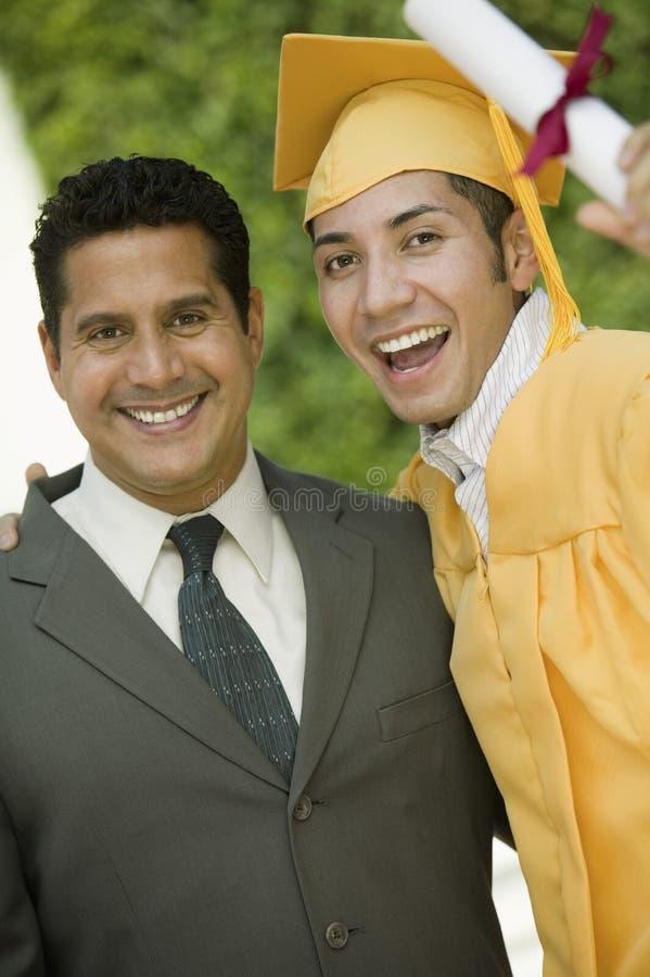 Diploma di sollevamento laureato con il braccio intorno al padre fotografia stock