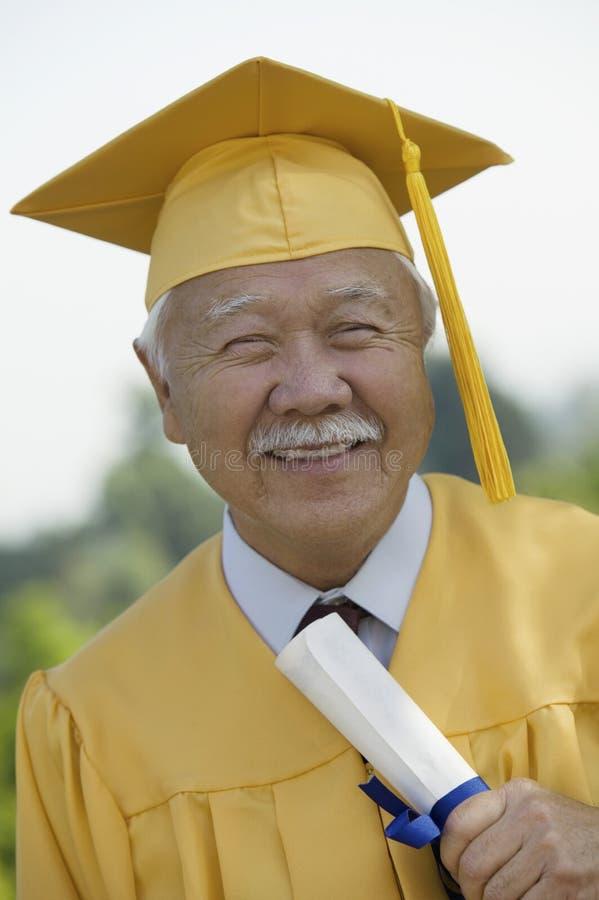 Diploma laureato della holding dell'anziano all'esterno fotografia stock