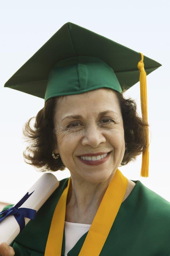 Diploma laureato della holding dell'anziano all'esterno fotografie stock