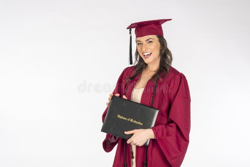 Diploma moreno bonito de Posing With A do modelo após a graduação contra um fundo branco imagens de stock