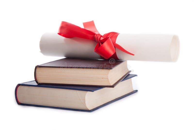 Diploma sobre a pilha de livros isolados no branco imagens de stock royalty free