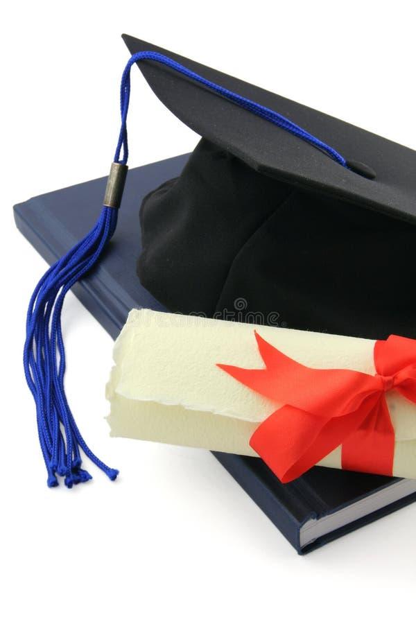 Diploma y casquillo de la graduación fotos de archivo