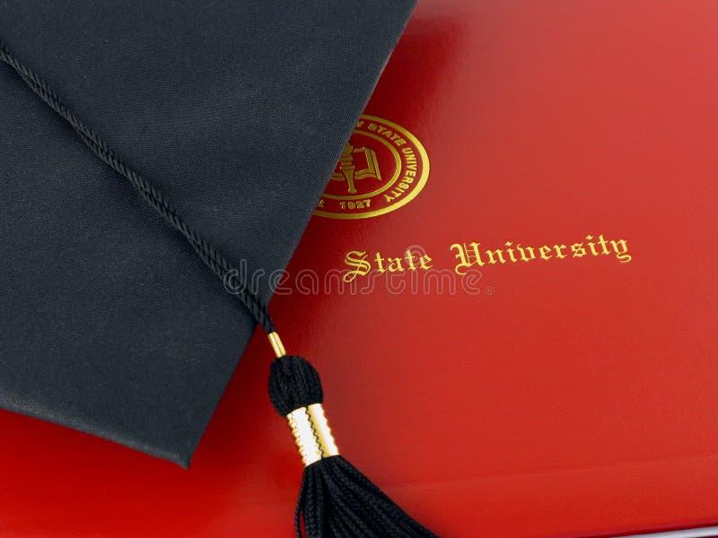 Diploma y casquillo de la universidad foto de archivo