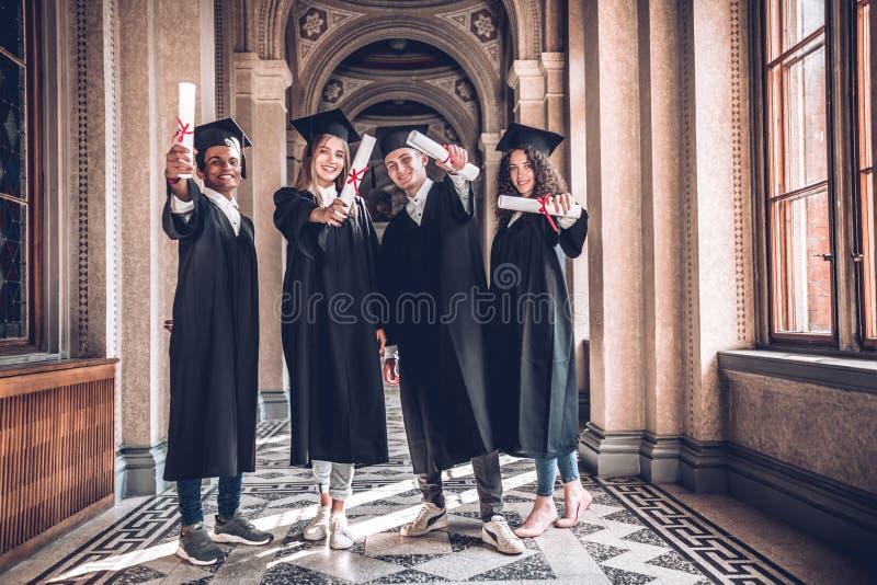 Diplomas na diversidade! Disparado de um grupo diverso de estudantes universitário que guardam seus diplomas foto de stock royalty free
