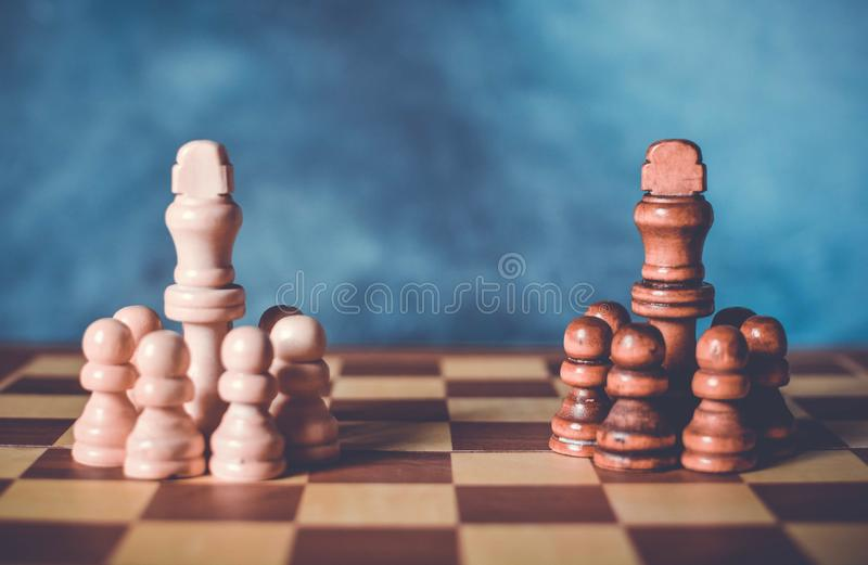 Diplomatic meeting of two teams concept with chess figures on a chessboard.  royalty free stock images