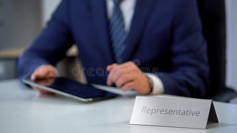 Diplomatic mission representative working on tablet, sliding and reading files. Stock photo royalty free stock photography