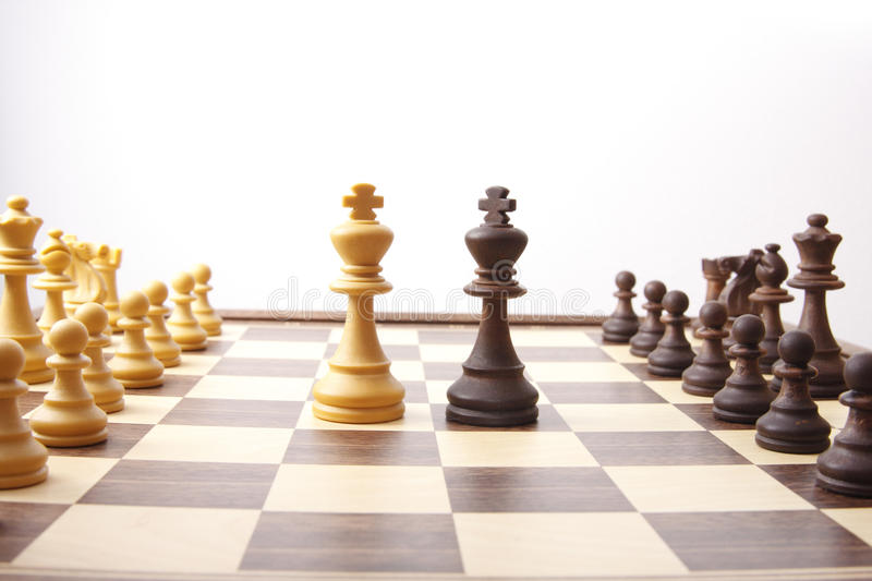 Diplomatic solution. Chessmen on chess board, kings meeting in the middle to find a diplomatic solution stock image