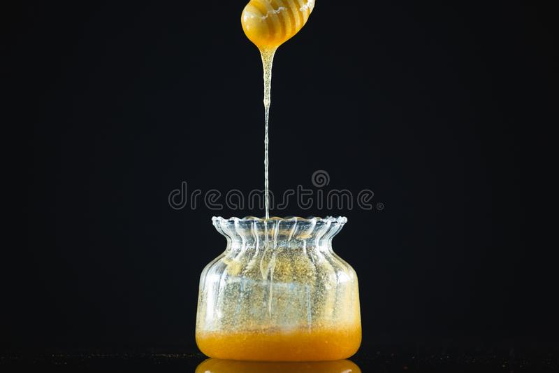Dipper μελιού με το ρέοντας μέλι στο βάζο γυαλιού στοκ φωτογραφία με δικαίωμα ελεύθερης χρήσης