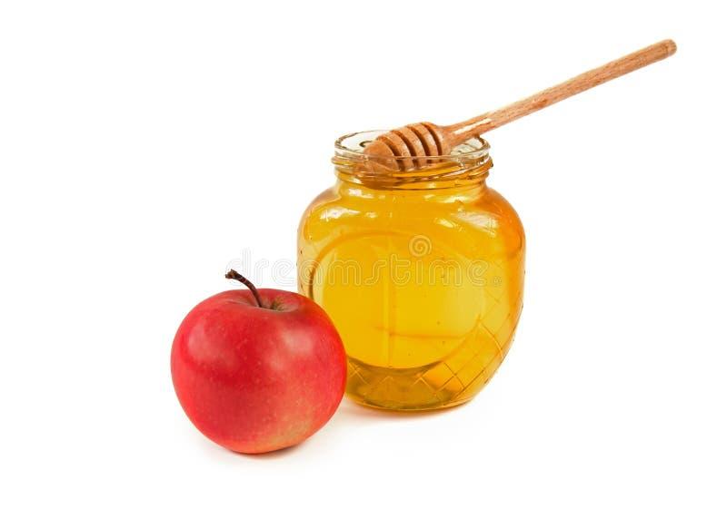 Dipper in een kruik honing met Apple op witte achtergrond royalty-vrije stock afbeeldingen