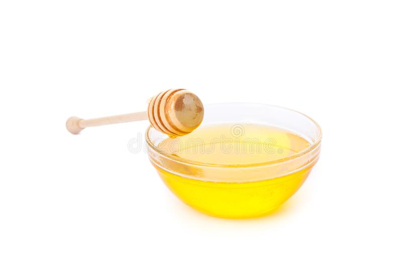 Dipper and honey in glass bowl isolated. On white background stock images