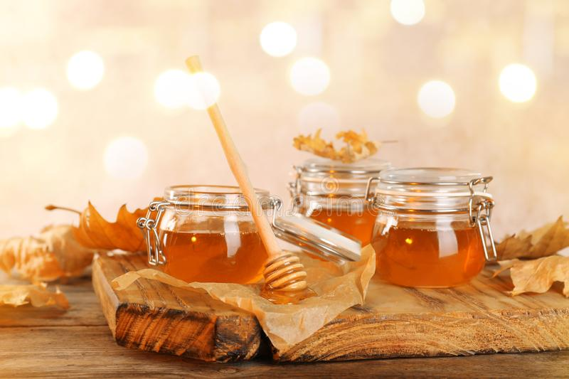 Dipper and jars with honey on table royalty free stock photos