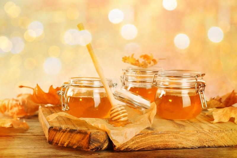 Dipper and jars with honey against blurred lights royalty free stock photos