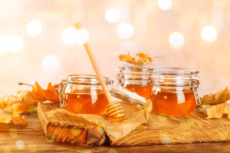 Dipper and jars with honey on table royalty free stock photo