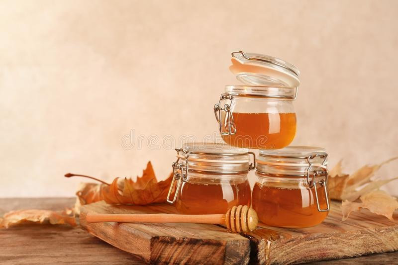 Dipper and jars with honey on table against color background. Space for text stock images