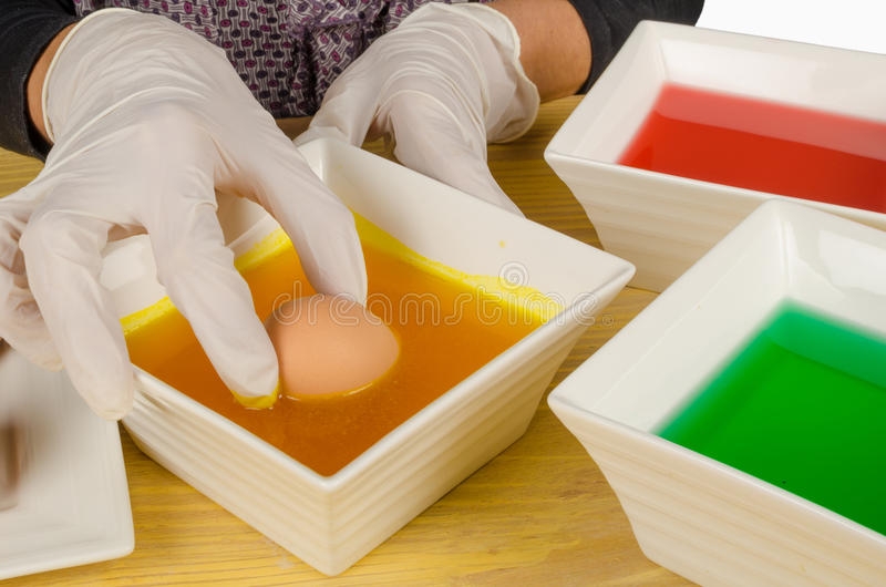 Dipping Easter eggs royalty free stock photos