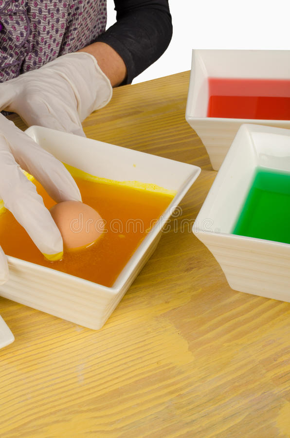 Dipping Easter eggs in yellow stock image