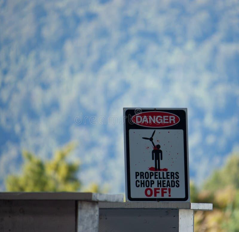 Dire del segno del pericolo: Il taglio delle eliche si dirige fuori! in un centro del paracadute vicino a Franz Josef in Nuova Ze fotografia stock libera da diritti