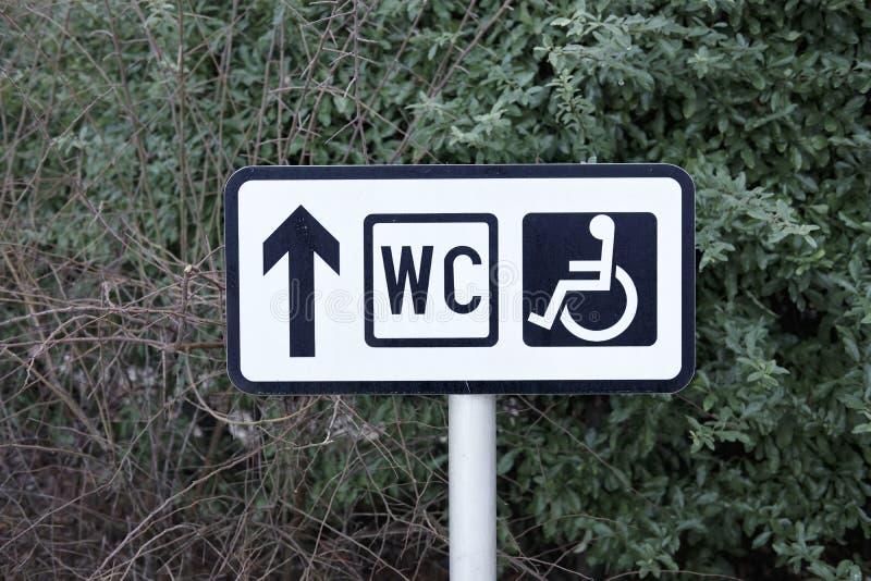 Dirección discapacitada de la flecha de los posts de muestra del retrete del WC del público fotos de archivo libres de regalías
